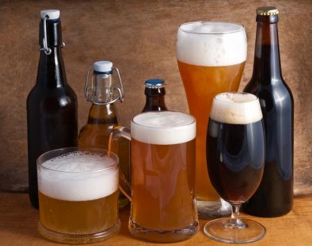 botellas de cerveza: El vidrio y botellas de cerveza en un fondo de madera