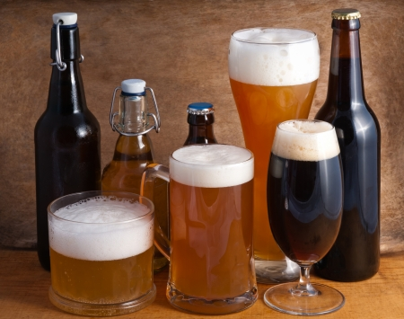 Glass and bottles of beer on a wooden background Stock Photo