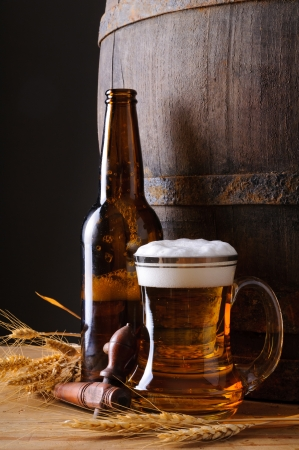 Still life with beer mug, bottle, grain and wooden barrel photo