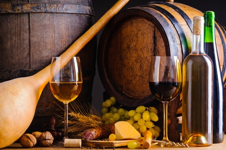 Winery background with traditional food, wineglass and wine bottles photo