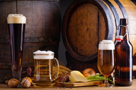 botellas de cerveza: Bodega la naturaleza muerta con la cerveza, la comida tradicional y barriles