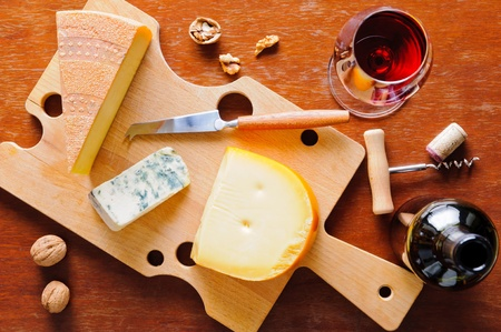 Gourmet cheese plate with glass and bottle of red wine photo