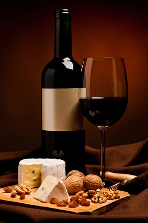 still life with glass and bottle of red wine and soft cheese snack photo