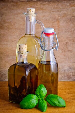 Bottles of olive oil and basil on a vintage background photo