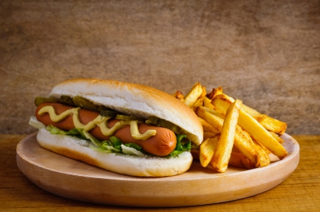 hotdog: Hot dog with french fries on a wooden plate