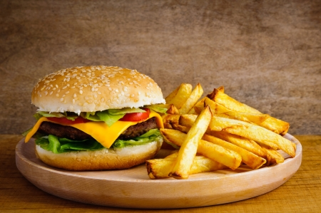 cheeseburgers: Fast food hamburger and french fries on a wooden plate