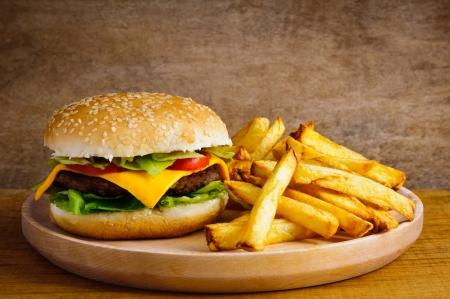 papas fritas: La comida rápida de hamburguesas y papas fritas francés en una placa de madera Foto de archivo