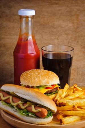 La comida rápida con hamburguesas, hot dogs, papas fritas francés, salsa de tomate y cola Foto de archivo - 13968846