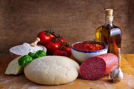 ingredient: Still life with traditional homemade salami pizza ingredients and dough