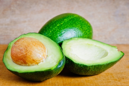 avocados: Ripe organic avocados on a wooden background