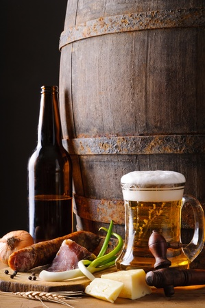 Still life composition with beer mug, wooden barrel and traditional food photo