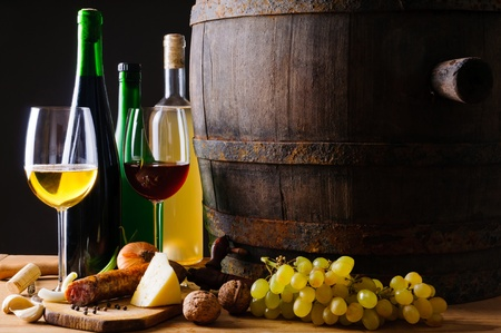 Still life composition with wine glasses, bottles and traditional food Stock Photo