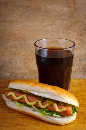 Hotdog menu and glass of cola on a wooden background photo