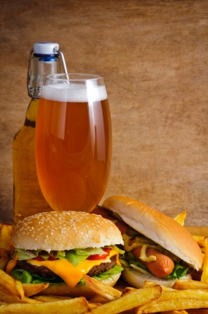 Fast food with cheeseburger, hot dog, fries and beer photo