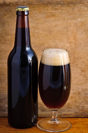 Glass and bottle of dark beer on a wooden background photo