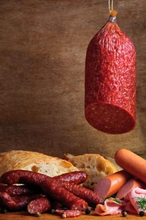 Stilleben mit traditionellen Speisen, Wurst und Brot auf einem Vintage-Holz-Hintergrund