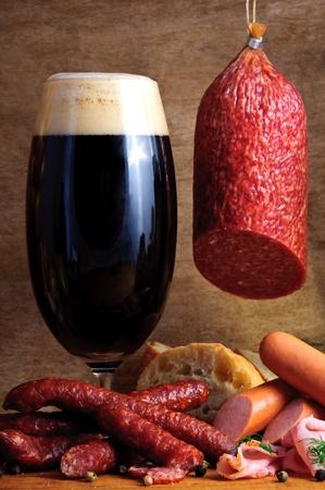salami: Naturaleza muerta con embutidos tradicionales y de vidrio de cerveza oscura