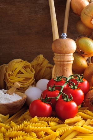 Still life with traditional italian pasta, ingredients and tomatoes photo