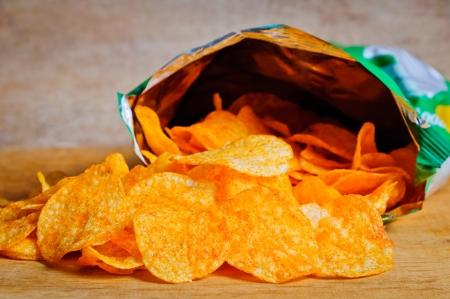tentempi�: Abra la bolsa de papas fritas Foto de archivo