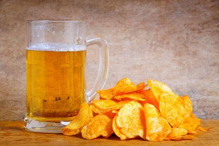 jarra de cerveza: Jarra de cerveza y papas fritas en un fondo de madera Foto de archivo