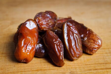 up to date: Dried dates on a wooden plate