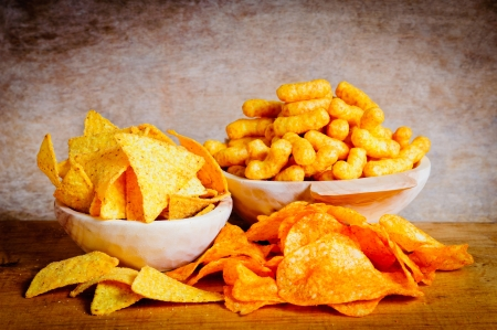 Chips, nachos and curls snacks on a wooden background Stock Photo