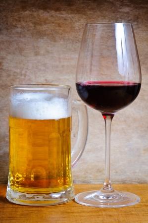 맥주 잔과 나무 배경에 와인 유리