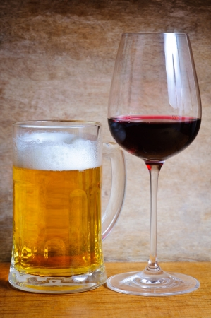beer and wine: Beer mug and wine glass on a wooden background