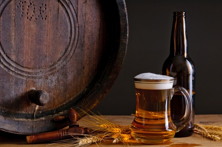 Still life composition with wooden barrel, glass and bottle of fresh beer photo