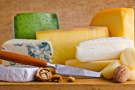 cheese platter: Still life with different cheese food and knife on a wooden plate