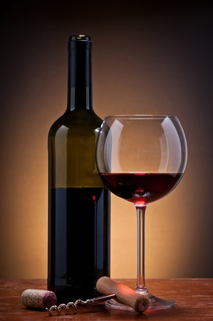 still life with red wine and warm orange background Stock Photo - 13994906