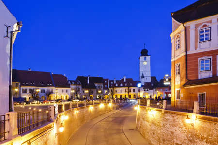 small square and council tower in sibiu, romania, at night photo