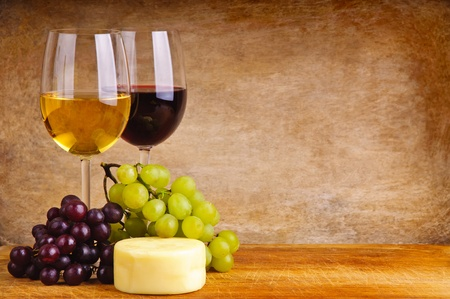 still lired and white wine, cheese and grapes on a wooden background with copy space