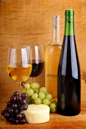 still life with cheese, grapes, red and white wine in bottles and glasses on a wooden background photo