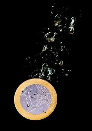 Concept with euro coin sinking in water over black background photo