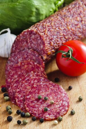 background with sliced italian salami on a wooden board photo