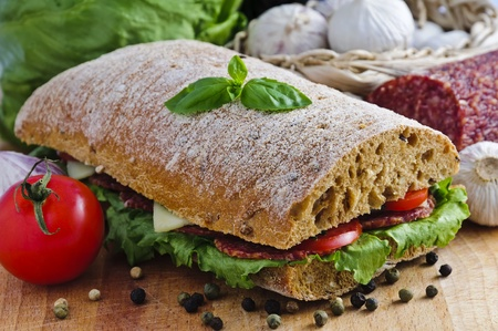 ciabatta sandwich with salami, cheese and vegetables Фото со стока