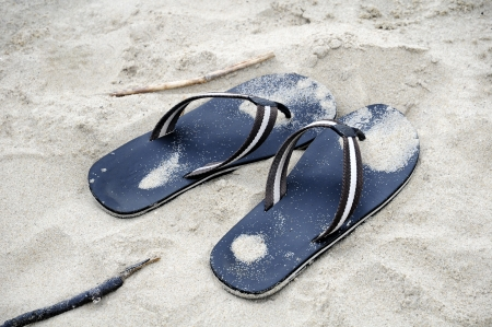 pair of black flip flops in sand beach photo