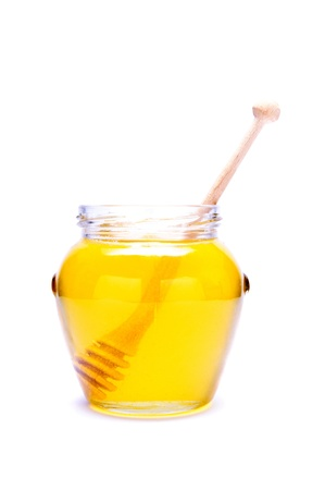 glass of honey with wooden dipper isolated on a white background Standard-Bild