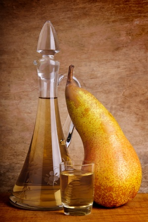 still life composition with traditional alcoholic drink and pear fruit on a vintage wooden background Stock Photo - 14653587