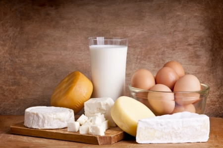 still life with dairy products, milk, chesse and eggs on a wooden backround Standard-Bild