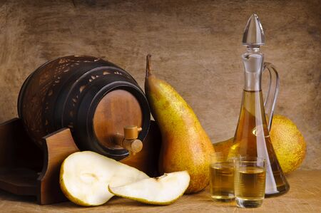 distillery: glasses and bottle of traditional fruit brandy with pear fruits and barrel on a wooden background Stock Photo