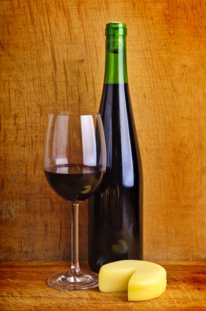 cheddar: glass and bottle of red wine with cheese on a wooden background