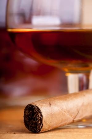 cigarro: Close up de cigarro con una copa de brandy en el fondo Foto de archivo