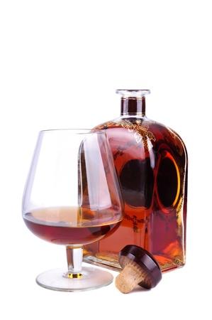 Glas und Flasche Cognac oder Brandy mit Kork auf weißem Hintergrund isoliert