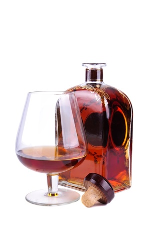 glass and bottle of cognac or brandy with cork isolated on a white background photo