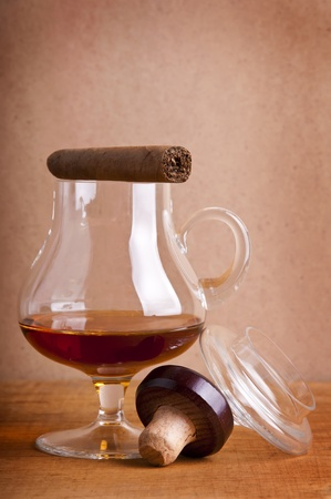 glass of cognac and cigar on a wooden background photo