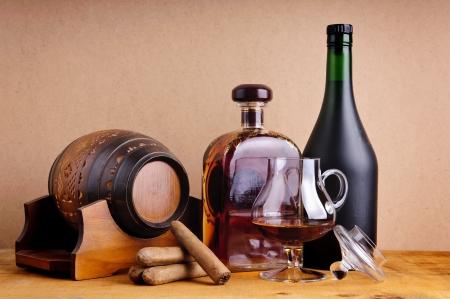 коньяк: Кубинские сигары и коньяк или бренди в стеклянные, бутылки и бочки на деревянном фоне Фото со стока