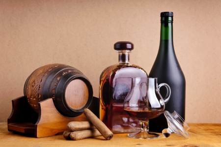 cuban cigars and cognac or brandy in glass, bottles and barrel on a wooden background Standard-Bild