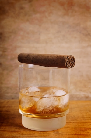glass of whiskey and cigar on a vintage wooden background photo